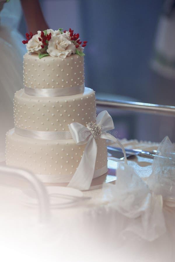 Den läckra tiered vita bröllopstårtan dekorerade med rosor och ett r royaltyfri bild
