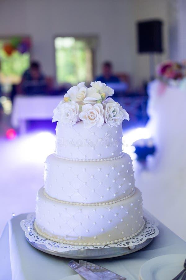 Den läckra tiered vita bröllopstårtan dekorerade med rosor på rece royaltyfria bilder