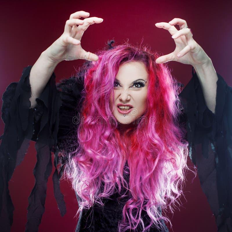 Den läskiga häxan med rött hår utför magi på en rosa bakgrund Allhelgonaafton fasatema royaltyfria bilder