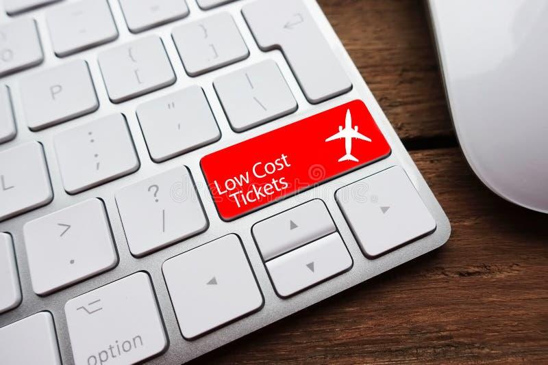 Den låga biljettprisen eller billiga flyg som begreppet möjligt av det vita datortangentbordet med low costbiljetter smsar på röt arkivfoto