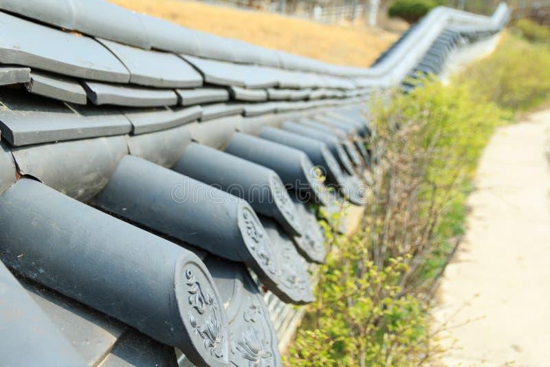 den låga trädgårdväggen som täckas med den koreanska traditionella taktegelplattan royaltyfri foto