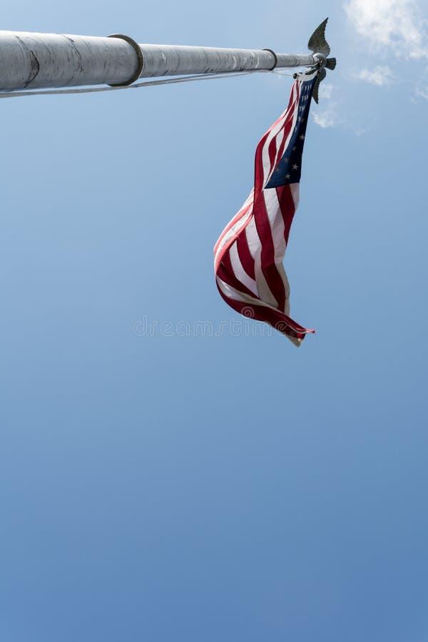 Den låga vinkeln sköt av amerikanska flaggan på tappningflaggstång royaltyfri bild