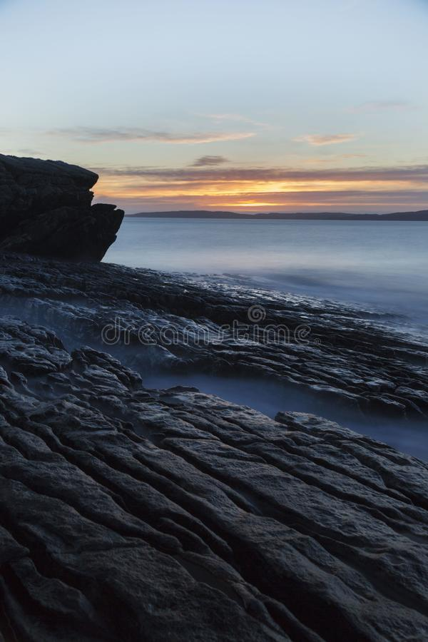 Den långa exponeringssolnedgången med havet vaggar på fotografering för bildbyråer
