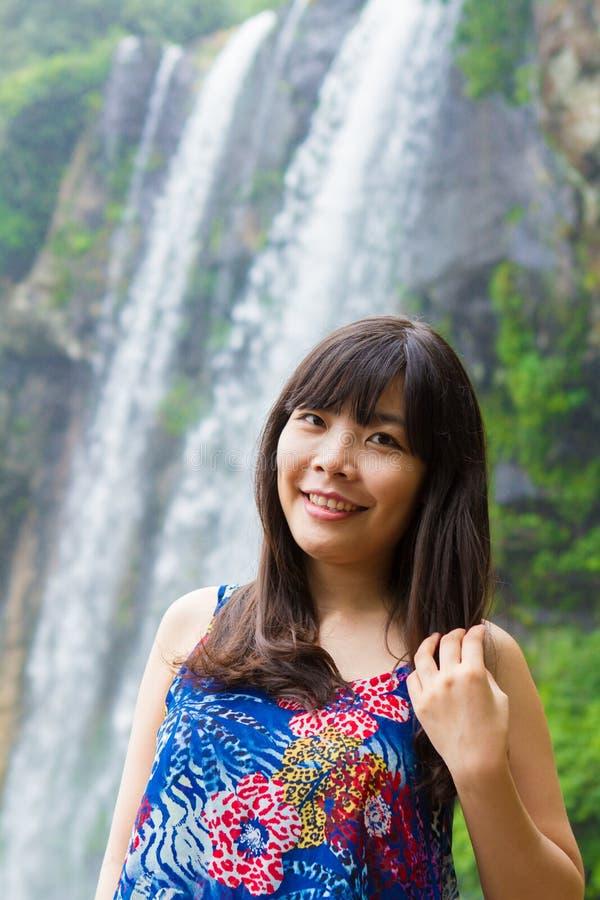 Den långa hårflickan spelar nära vattenfallet royaltyfri foto