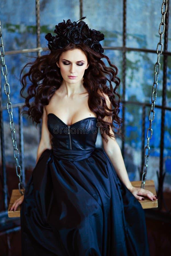 Den långa haired sinnliga brunetten med en krans av svart blommar sitt royaltyfri bild
