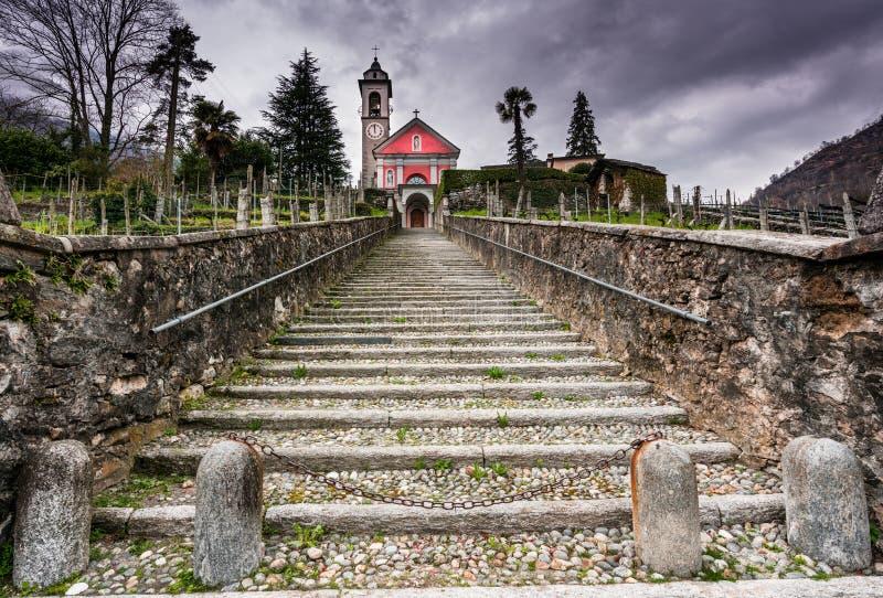 Den långa trappan som leder en gammal ros, färgade upp till kyrkan under en uttrycksfull mulen himmel royaltyfri bild