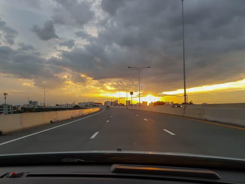 Den långa vägen med solnedgång arkivbild