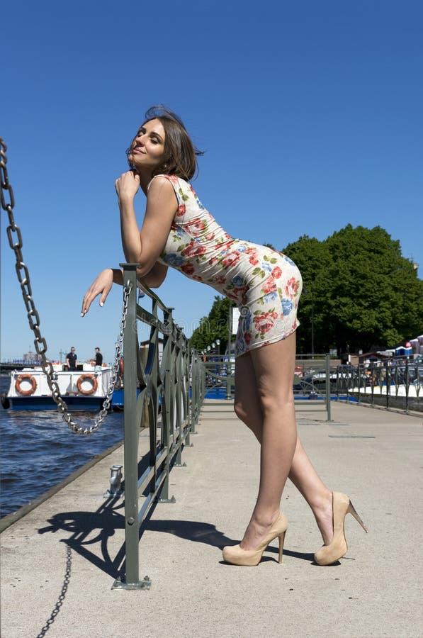 Den långbenta flickan i kort klänning står på riverfronten på en solig da royaltyfria bilder