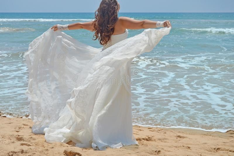 Den långhåriga brunettbruden rätar ut hennes klänninganseende på sanden, flicka ser upp på himlen på stranden på Indiska oceanen  arkivbilder