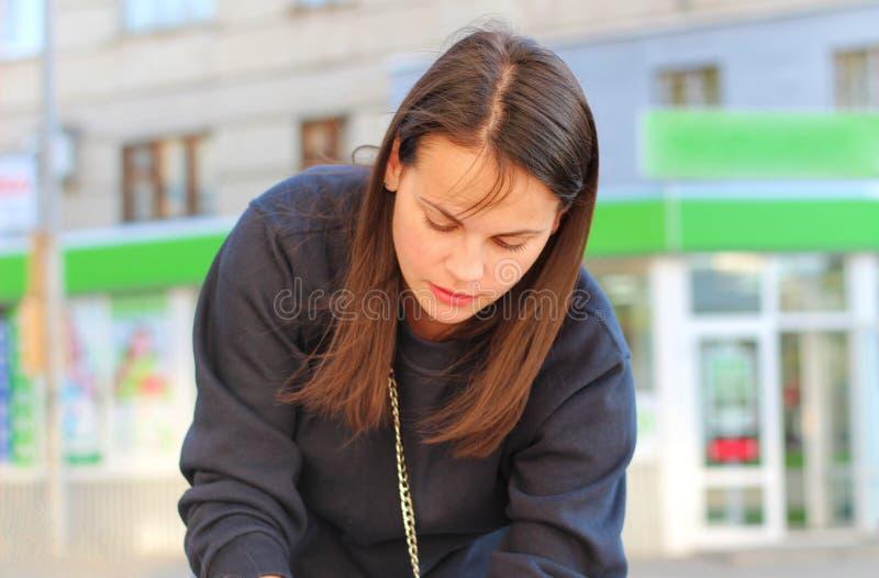 den långhåriga brunettflickan lutar över pramen på bakgrunden av shoppar fönster Stående av en europeisk kvinna i en blå tröja arkivbilder