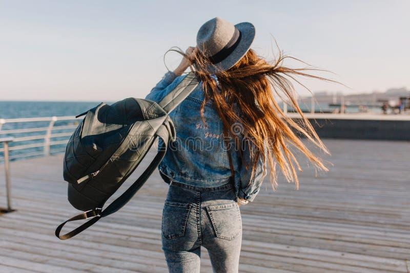 Den långhåriga brunettflickan tycker om frihet som spenderar tid på pir i en blåsig morgon Bärande hatt för ursnygg slank flicka royaltyfri foto