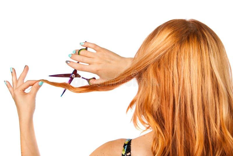Den långhåriga rödhåriga flickan med sax klipper håret royaltyfria foton