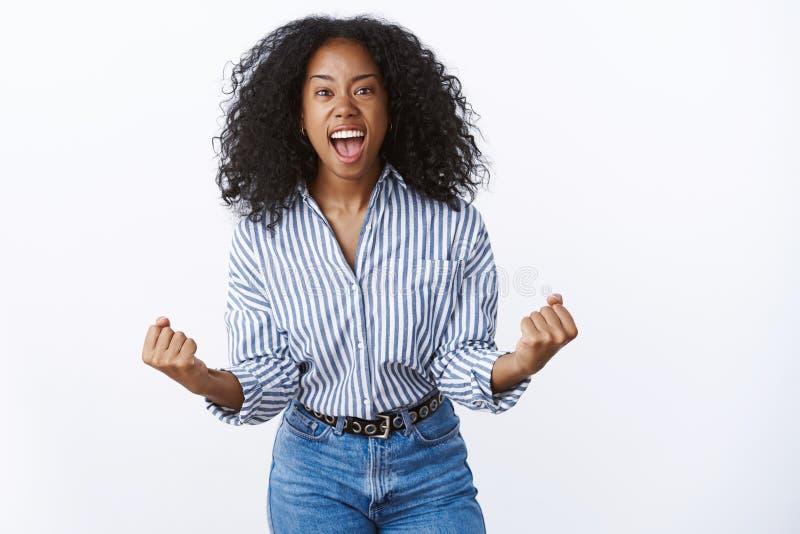 Den lösa upphetsade förkrossade attraktiva afrikansk amerikankvinnan ropar ut högt lyckligt seger för knytnävesegergest royaltyfri fotografi