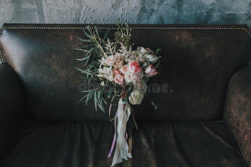 Den lantliga bröllopbuketten med ljusa rosor och andra blommor på en lyx bryner soffan Närbild royaltyfri bild