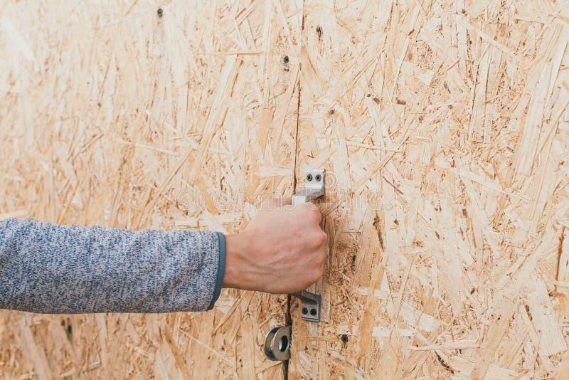 Den lantliga gamla dörren av sågspån en man öppnar en trädörr sågspån tryckte på in i dörren arkivbild