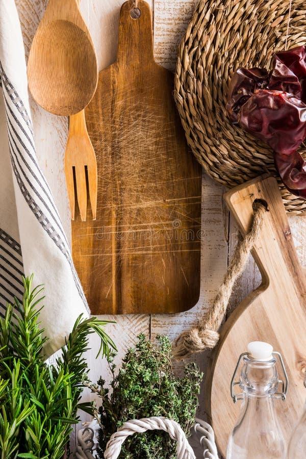 Den lantliga Provence kökinre, ny örtrosmarintimjan, wood skärbrädor, redskap, linnehandduk, torkade peppar, glass bot arkivbild