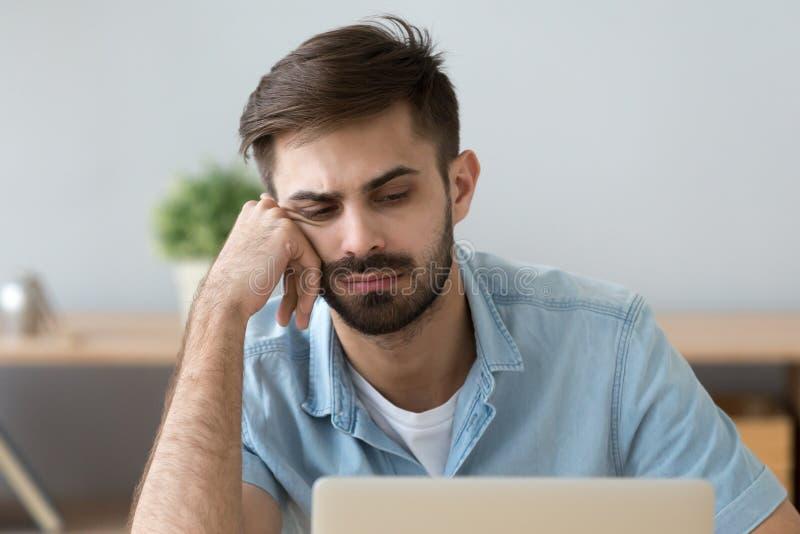 Den lata mannen känner omotiverat sammanträde nära bärbara datorn hemma royaltyfri bild