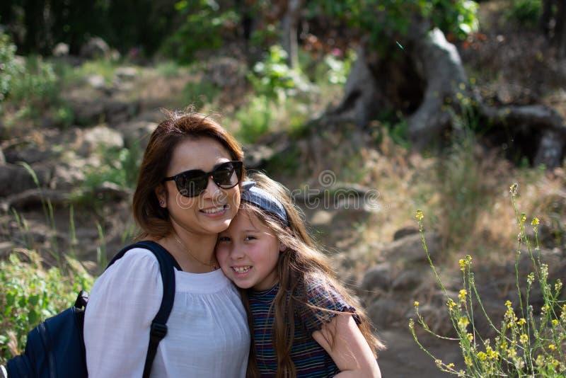 Den Latina kvinnan och dottern som tillsammans ler, medan stå, av trän på parkerar framme royaltyfria bilder