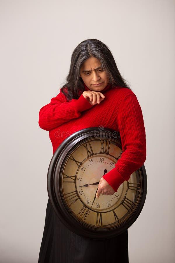 Den latinamerikanska kvinnan rymmer klockan, medan t?nka av framtid royaltyfri foto