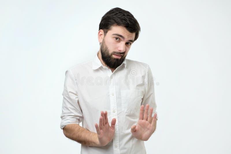 Den latinamerikanska mannen som gör skrämd gest med hans, gömma i handflatan som, om försöka att försvara sig från någon arkivbilder
