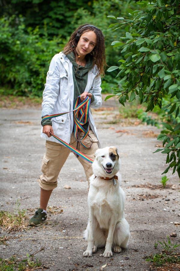 Den Latino flickan med dreadlocks håller en hund på en koppel Sommar bakgrund suddighet green Kommunikation med djuret arkivbild