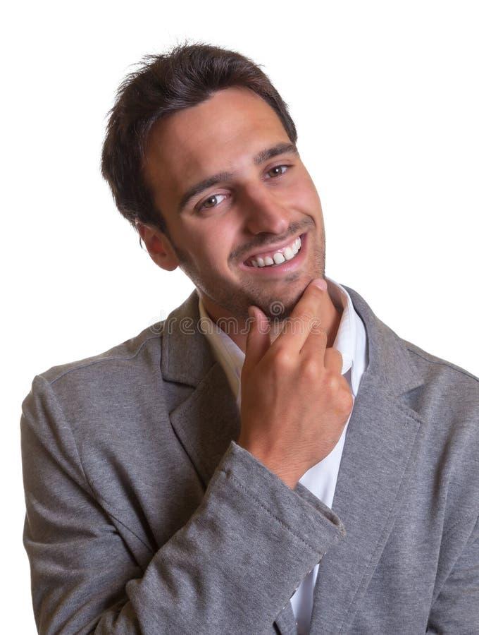 Den latinska affärsmannen i grå färger passar att skratta på kameran arkivfoto