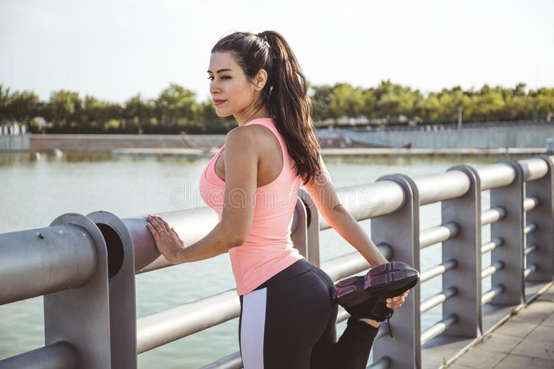 Den latinska kvinnan har en muskel som sträcker sig framför en sjö och är klädd i rosa och svarta byxor royaltyfri bild