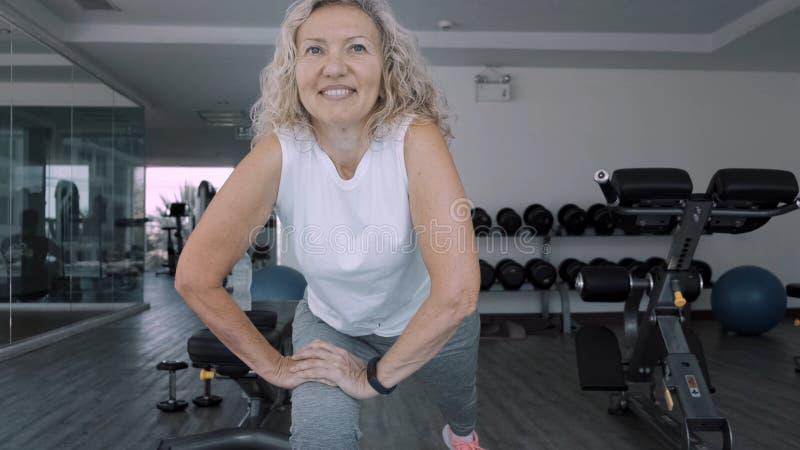 Den ?ldre kvinnan g?r squattings i idrottshallen Gör den höga kvinnan för den äldre kvinnan övningar för en sport i idrottshallen royaltyfria foton