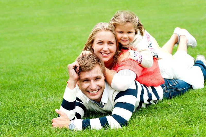 Den le familjen av tre travde överst av varje annan arkivfoton