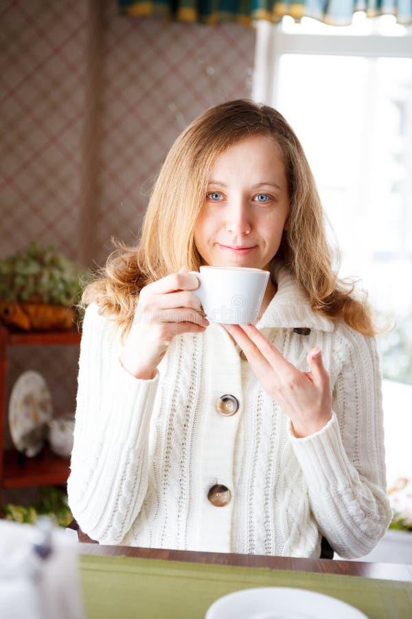 Den le flickan med en kupa av kaffe räcker in royaltyfri bild