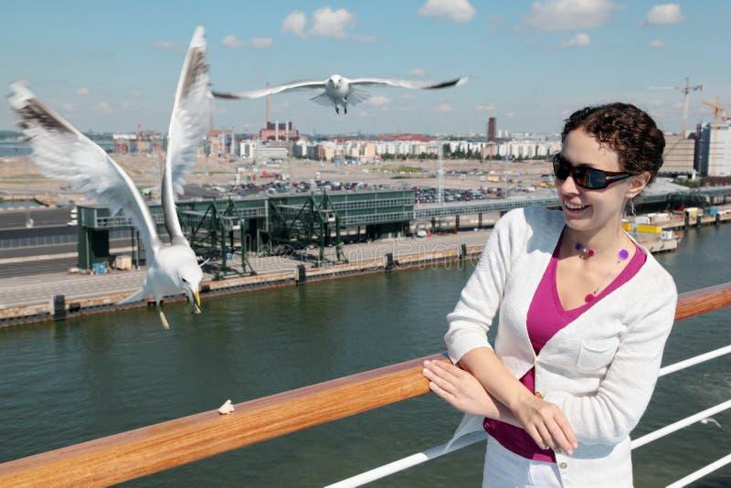 Den le kvinnan matar seagulls på däck av shipen royaltyfria bilder