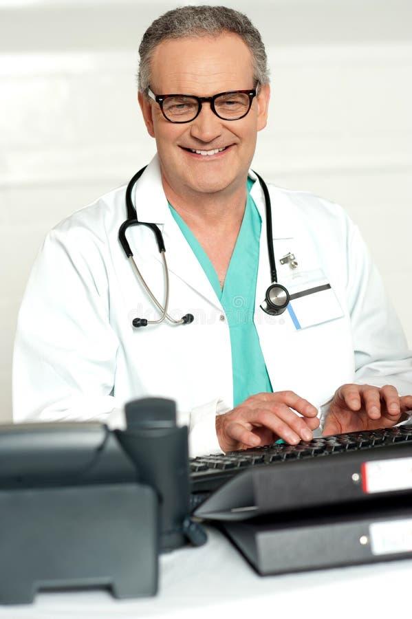 Den le läkaren i öga slitage skrivande på tangentbordet royaltyfri foto