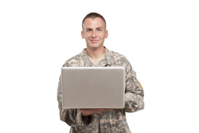 Caucasian soldattyper på en bärbar dator royaltyfri foto