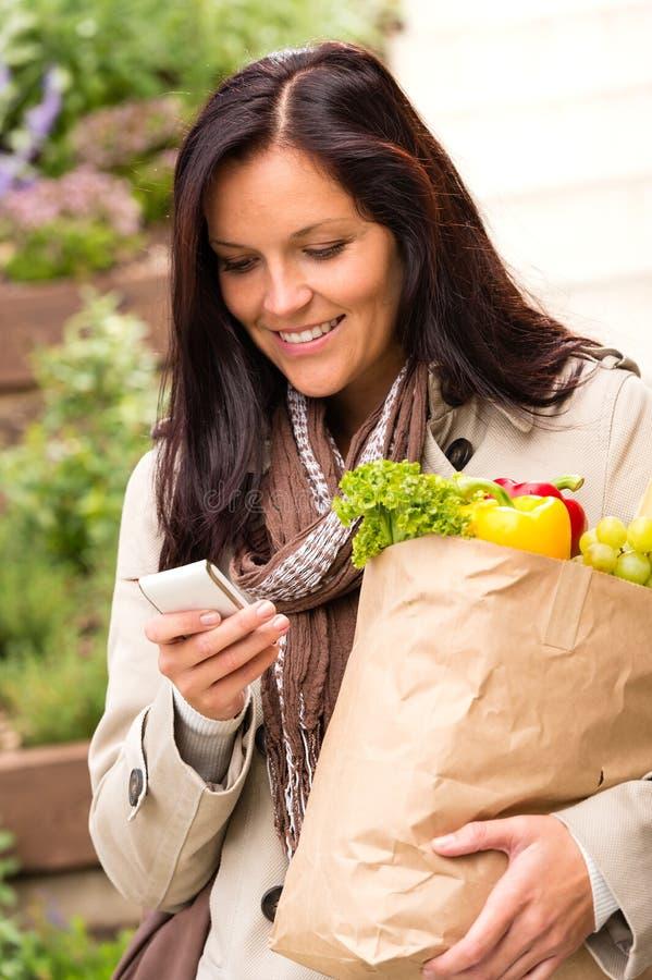 Den le mobilen för kvinnashoppinggrönsaker ringer sms fotografering för bildbyråer