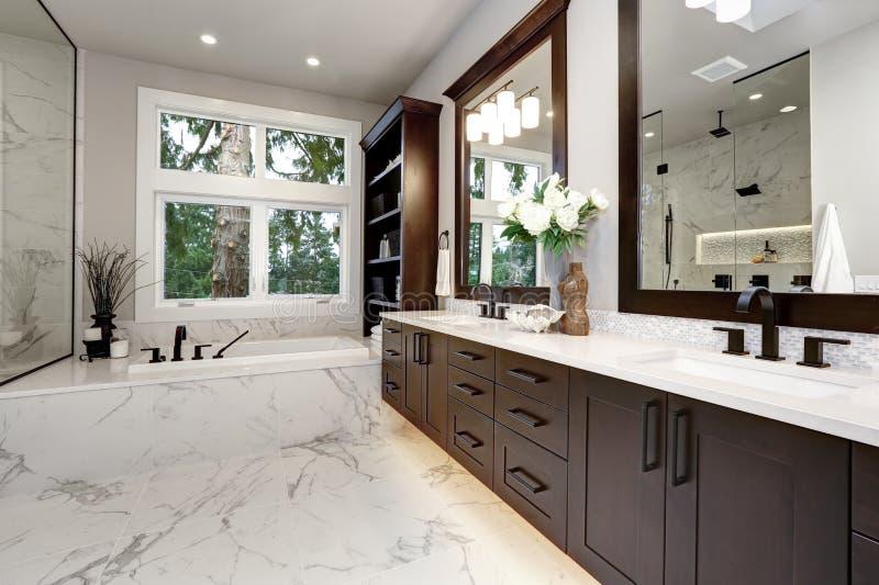 Den ledar- badruminre i det lyxiga moderna hemmet med mörka ädelträkabinetter, vit badar och den glass dörrduschen royaltyfria bilder