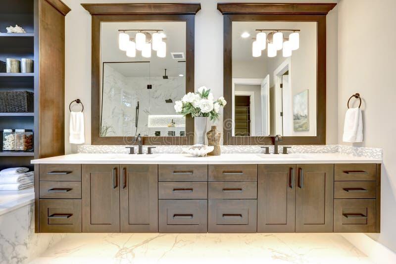 Den ledar- badruminre i det lyxiga moderna hemmet med mörka ädelträkabinetter, vit badar och den glass dörrduschen royaltyfri foto