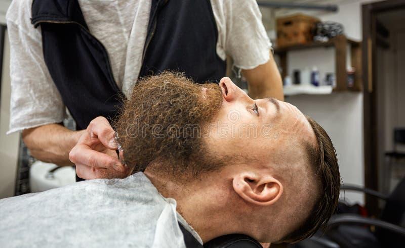 Den ledar- barberaren gör frisyren och att utforma Begreppsfrisersalong Sk?ggutforma och snitt utforma av det svarta skägget S? m arkivfoton