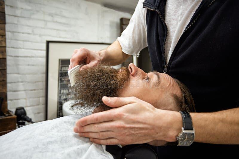 Den ledar- barberaren g?r frisyren och att utforma Begreppsfrisersalong Sk?ggutforma och snitt utforma av det svarta sk?gget S? m royaltyfri fotografi