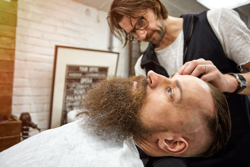 Den ledar- barberaren g?r frisyren och att utforma Begreppsfrisersalong Sk?ggutforma och snitt utforma av det svarta sk?gget S? m fotografering för bildbyråer