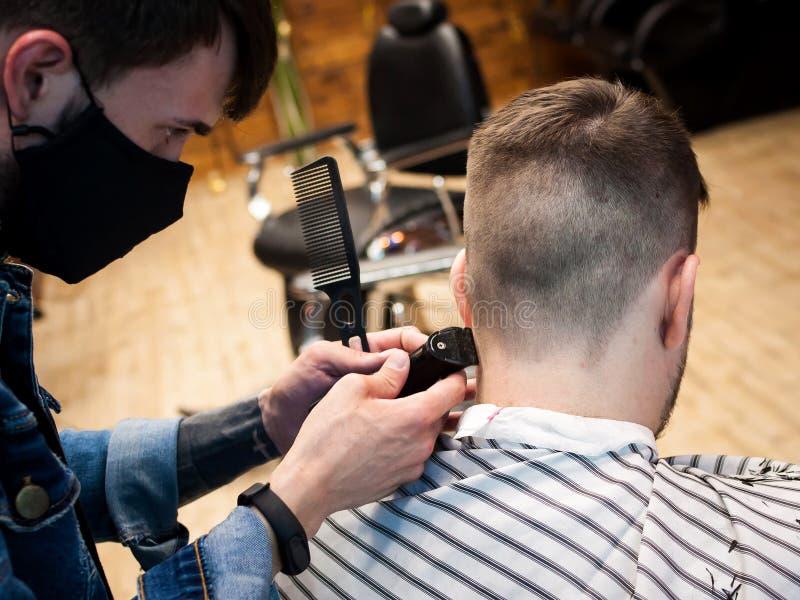 Den ledar- frisören klipper en man i salongen arkivfoton