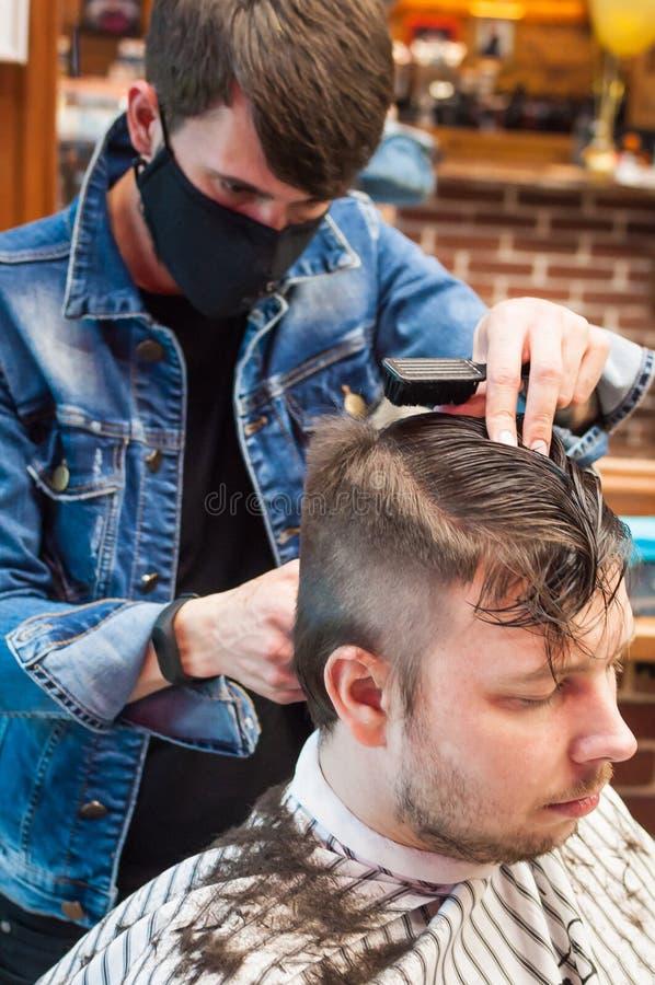Den ledar- frisören klipper en man i salongen fotografering för bildbyråer