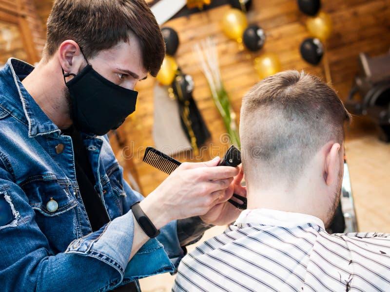 Den ledar- frisören klipper en man i salongen arkivbild