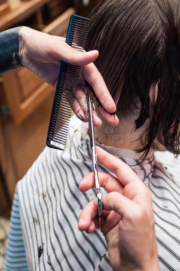 Den ledar- frisören klipper en man i salongen royaltyfri foto