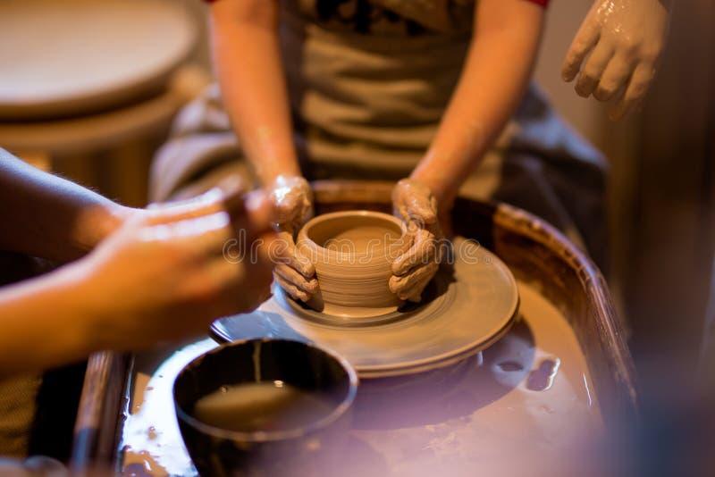 Den ledar- keramikern undervisar barnet att arbeta på hjulet för keramiker` s Slut som skjutas upp royaltyfri bild