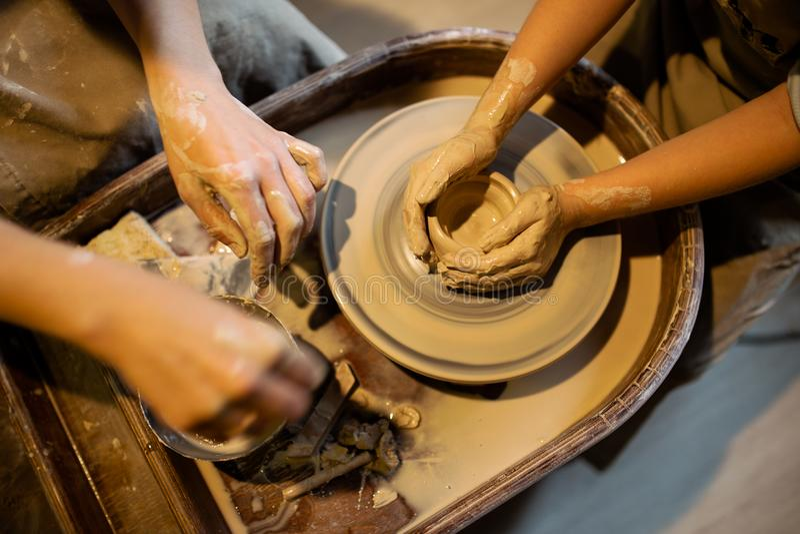 Den ledar- keramikern undervisar barnet att arbeta på hjulet för keramiker` s Slut som skjutas upp royaltyfri fotografi