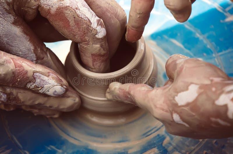 Den ledar- keramikern undervisar barnet hur man gör en kanna på en krukmakeri att rulla arkivfoto