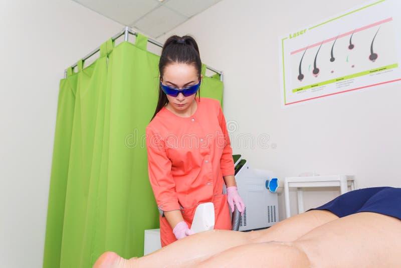 Den ledar- kosmetologen tar bort hår med laser-hårborttagning Tillvägagångssättet av laser-hårborttagning av benen royaltyfri fotografi
