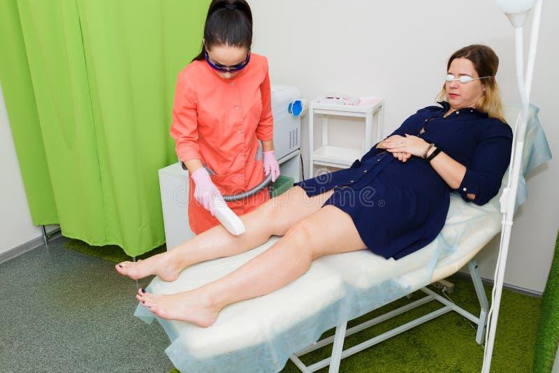 Den ledar- kosmetologen tar bort hår med laser-hårborttagning Tillvägagångssättet av laser-hårborttagning av benen royaltyfri bild