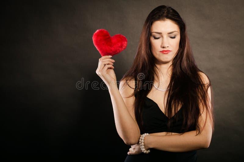 Den ledsna älskvärda kvinnan rymmer röd hjärta på svart arkivfoto