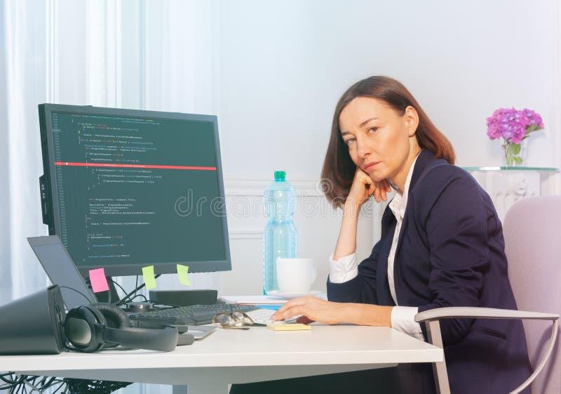 Den ledsna affärskvinnan arbetar på datoren i kontoret fotografering för bildbyråer